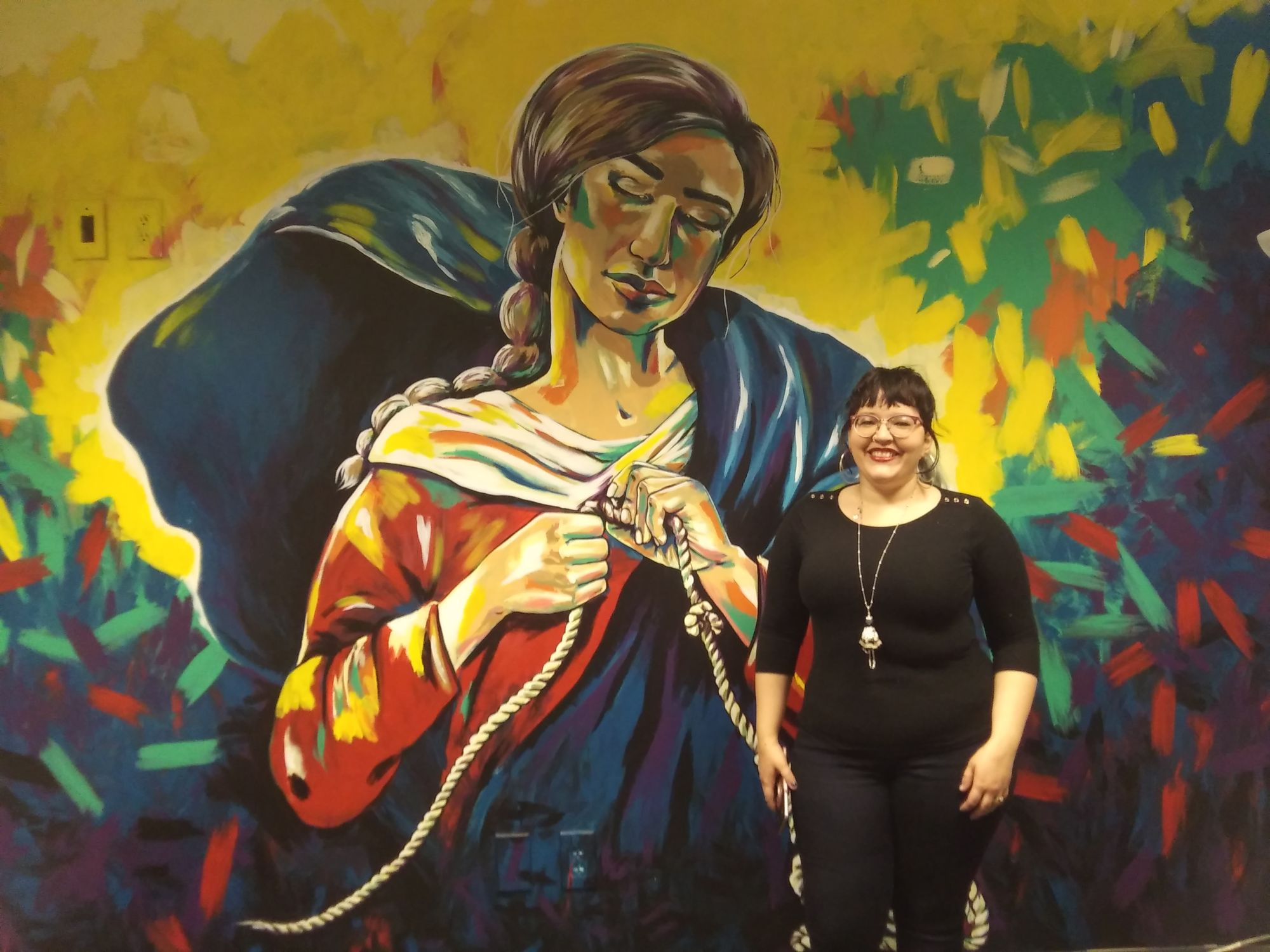 Local artist paints free hand mural on campus